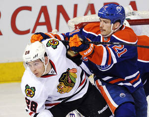 Photo - Edmonton Oilers' Andrew Ference (21) defends Chicago Blackhawks' Ben Smith (28) during the second period of an NHL hockey game in Edmonton, Alberta, on Monday, Nov. 25, 2013. (AP Photo/The Canadian Press, John Ulan)