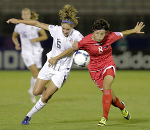 Photo -   Morgan Brian of the United States, left, and Jon Myong Hwa of North Korea battle for the ball during their quarterfinal soccer match of the U-20 Women's World Cup in Urawa, near Tokyo, Friday, Aug. 31, 2012. (AP Photo/Koji Sasahara)
