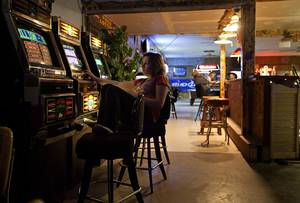 Photo - Jaycee May, a bartender at Swett Tavern, plays a video lottery machine on Thursday, June 26, 2014 at Swett Tavern, in Swett, S.D. A businessman is selling the small, southeastern South Dakota town for $400,000. (AP Photo/Rapid City Journal, Eric Ginnard)