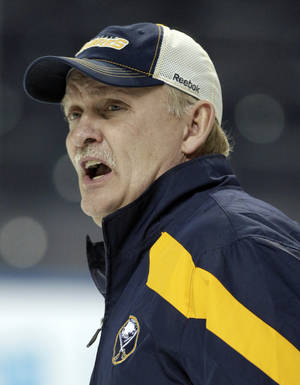 photo - FILE - In this Jan. 11, 2012, file photo, Buffalo Sabres coach Lindy Ruff talks with players during NHL hockey practice in Buffalo, N.Y. Ruff was fired on Wednesday, Feb. 20, 2013, after the team's latest slow start to the season and amid growing criticism from the team's fan base. (AP Photo/David Duprey, File)