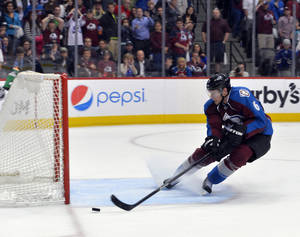 Photo - Colorado Avalanche defenseman Erik Johnson (6) saves the empty net goal by the Minnesota Wild during the third period in Game 1 of an NHL hockey first-round playoff series on Thursday, April 17, 2014, in Denver. (AP Photo/Jack Dempsey)