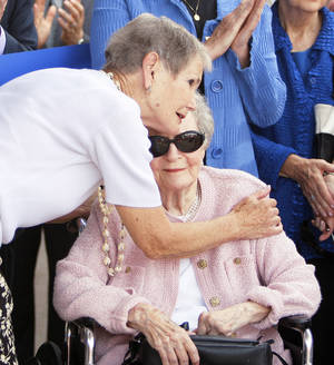 photo - Patience S. Latting receives a hug from former employee Fran Cory during the  opening of the new  library.