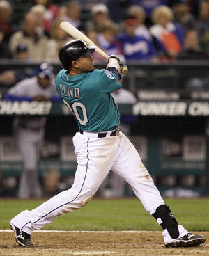 Photo -   Seattle Mariners' Miguel Olivo hits a two-run home run in the eighth inning of a baseball game against the Texas Rangers, Friday, Sept. 21, 2012, in Seattle. (AP Photo/Ted S. Warren)