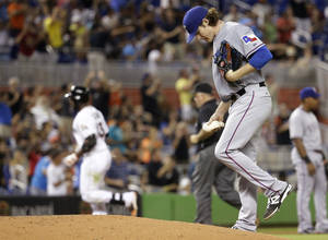 Photo - Texas Rangers starting pitcher Miles Mikolas right, kicks the mound as Miami Marlins' Marcell Ozuna, left, rounds third base after hitting a solo home run in the fourth inning during a baseball game, Tuesday, Aug. 19, 2014, in Miami. (AP Photo/Lynne Sladky)