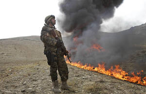 Photo -   An Afghan counternarcotic policeman (CNPA) secures the area as 25 tons of drugs and drug-making gear are burned on the outskirts of Kabul, Afghanistan, Sunday, Oct. 14, 2012. The 25 tons of drugs and paraphernalia where confiscated over the past nine months in the Kabul area. (AP Photo/Ahmad Jamshid)