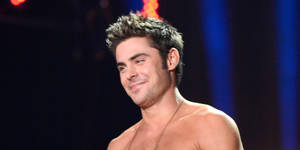 Photo - LOS ANGELES, CA - APRIL 13:  Actor Zac Efron speaks onstage at the 2014 MTV Movie Awards at Nokia Theatre L.A. Live on April 13, 2014 in Los Angeles, California.  (Photo by Kevin Mazur/WireImage)