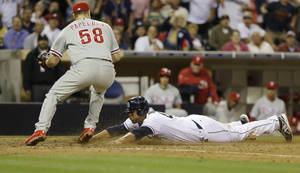 Photo - San Diego Padres' Kyle Blanks is safe at home while scoring on a wild pitch as Philadelphia Phillies relief pitcher Jonathan Papelbon goes for a late tag in the ninth inning of a baseball game in San Diego, Monday, June 24, 2013.  The run tied the game as the Padres scored three runs in the ninth. (AP Photo/Lenny Ignelzi)