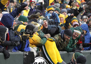 Photo - Green Bay Packers' Eddie Lacy celebrates with fans after hit touchdown run during the first half of an NFL football game against the Atlanta Falcons Sunday, Dec. 8, 2013, in Green Bay, Wis. (AP Photo/Mike Roemer)