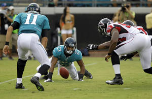 photo -   Jacksonville Jaguars running back Rashad Jennings (23) fumbles the ball on a handoff from quarterback Blaine Gabbert (11) as Atlanta Falcons defensive tackle Vance Walker, right, recovers the ball during the first half of an NFL preseason football game on Thursday, Aug. 30, 2012, in Jacksonville, Fla. (AP Photo/John Raoux)