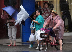 Photo - Taiwanese women hold their umbrellas against powerful gusts of wind as Typhoon Fitow approaches in Taipei, Taiwan, Sunday, Oct. 6, 2013. (AP Photo/Chiang Ying-ying)