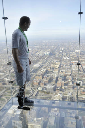 "Photo -   Zac Vawter stands on ""The Ledge"" of the Willis Tower in Chicago after walking up the stairs of the building Sunday, Nov. 4, 2012, to become the first person to climb the 103 floors of one of the world's tallest skyscrapers with a bionic leg. Vawter was wearing a prosthetic leg controlled by his mind while participating in ""SkyRise Chicago."" (AP Photo/Chicago Sun-Times, Brian Jackson) CHICAGO LOCALS OUT, MAGS OUT"