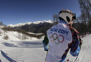 Photo - Olympic worker Pavel Dovgiy prepares to ski down the Alpine course ahead of the 2014 Sochi Winter Olympics, Tuesday, Feb. 4, 2014, in Krasnaya Polyana, Russia. (AP Photo/Charles Krupa)
