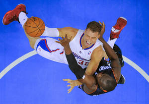 Photo - Los Angeles Clippers forward Blake Griffin, top, drives to the basket over Charlotte Bobcats forward Bismack Biyombo during the first half of an NBA basketball game in Los Angeles, Tuesday, Feb. 26, 2013. (AP Photo/Chris Carlson)