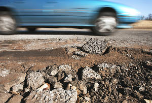 photo - A car avoids a large pothole on SW 9 near Western Avenue on Thursday morning.  PHOTO BY Jim Beckel, The Oklahoman