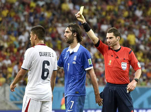 Photo - Referee Benjamin Williams, of Australia, right, gives Costa Rica's Oscar Duarte a yellow card during the World Cup round of 16 soccer match between Costa Rica and Greece at the Arena Pernambuco in Recife, Brazil, Sunday, June 29, 2014. (AP Photo/Martin Meissner)