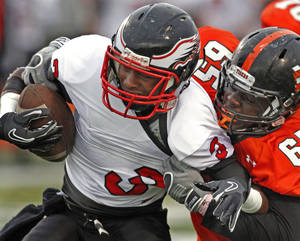 Photo - HIGH SCHOOL FOOTBALL: Del City's Corey Lawrence (3) is dragged down on the opening series by Ayo Oyesanya (65) as the Norman High School Tigers play the Del City Eagles on Thursday, September 15, 2011, in Norman, Okla.   Photo by Steve Sisney, The Oklahoman ORG XMIT: KOD