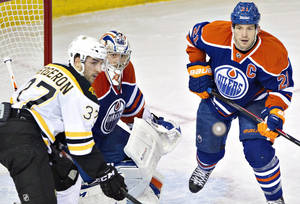 Photo - Boston Bruins' Patrice Bergeron (37), Edmonton Oilers goalie Jason LaBarbera (1) and Oilers' Andrew Ference (21) look for the rebound  during the second period of an NHL hockey game, Thursday, Dec. 12, 2013 in Edmonton, Alberta. (AP Photo/The Canadian Press, Jason Franson)
