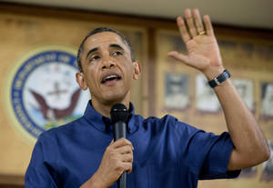 Photo - President Barack Obama speaks to members of the military and their families in Anderson Hall at Marine Corps Base Hawaii, Wednesday, Dec. 25, 2013, in Kaneohe Bay, Hawaii. The first family is in Hawaii for their annual holiday vacation. (AP Photo/Carolyn Kaster)