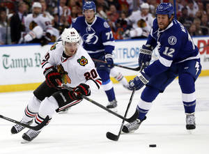 Photo - Tampa Bay Lightning left wing Ryan Malone (12) tries to catch Chicago Blackhawks left wing Brandon Saad (20) during the first period of an NHL hockey game on Thursday, Oct. 24, 2013, in Tampa, Fla. (AP Photo/Reinhold Matay)