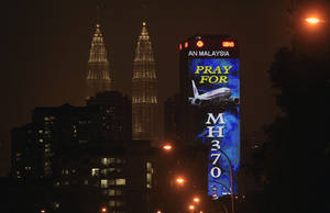 """Photo - An office building is illuminated with LED lights displaying """"Pray for MH370"""" next to Malaysia's landmark Petronas Twin Towers in Kuala Lumpur, Malaysia, Wednesday, March 19, 2014. Countless theories have surfaced about the disappearance of Malaysia Airlines Flight 370 nearly two weeks ago. (AP Photo/Lai Seng Sin)"""