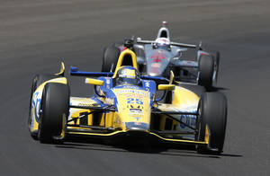 Photo - Marco Andretti leads Scott Dixon, of New Zealand, through the first turn during the 98th running of the Indianapolis 500 IndyCar auto race at the Indianapolis Motor Speedway in Indianapolis, Sunday, May 25, 2014. (AP Photo/Tom Strattman)
