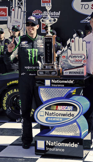 Photo - Driver Kyle Busch (54) stand with the trophy after winning the NASCAR Nationwide series auto race at Bristol Motor Speedway on Saturday, March 15, 2014, in Bristol, Tenn. (AP Photo/Wade Payne)