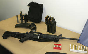 Photo - FILE - This March 27, 2006 file photo, shows a Bushmaster AR-15 semi-automatic rifle and ammunition on display at the Seattle Police headquarters in Seattle. The maker of the Bushmaster rapid-fire weapon used to kill schoolchildren in Connecticut on Friday, Dec. 14, 2012, was put up for sale on Tuesday, Dec. 18, 2012, as investors soured on the gun business. (AP Photo/Ted S. Warren, File)