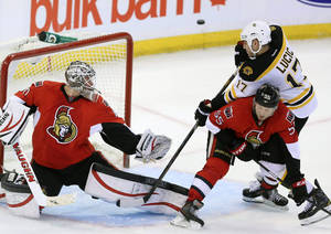 photo - Boston Bruins Milan Lucic (17) attempts to deflect a flying puck as he is cheked Ottawa Senator Sergei Gonchar (55)during second period NHL hockey action in Ottawa Monday March 11, 2013.  (AP Photo/The  Canadian Press, Fred Chartrand)