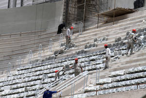 Photo - FILE - In this Jan. 21, 2014 file photo released by Portal da Copa, workers install seats at the Arena da Baixada stadium in Curitiba, Brazil. The southern city of Curitiba is expected to remain in the World Cup despite construction delays on its stadium, Brazilian Sports Minister Aldo Rebelo said Wednesday, Feb. 5, 2014. During a visit to the city, he expressed confidence that local organizers will be able to show FIFA that the stadium will be ready in time to hold its four matches scheduled for football's showcase event in June. (AP Photo/Portal da Copa, Paulino Menezes, File)