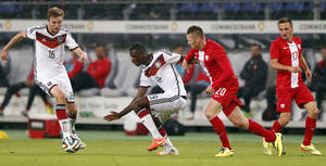 Photo - Germany's Christoph Kramer, from left, Germany's Antonio Ruediger and Poland's  Marcin Robak challenge for the ball during a friendly soccer match between Germany and Poland in Hamburg, Germany, Tuesday, May 13, 2014.  (AP Photo/Matthias Schrader)