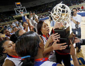 Photo - The Millwood team, including Quira Demery lift the trophy following their 64-50 win over Prague in the Class 3A girls high school state basketball championship game at State Fair Arena in Oklahoma City, Saturday, March 10, 2012. Photo by Bryan Terry, The Oklahoman
