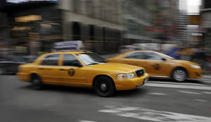 Photo -  New York City taxis drive through Times Square. Uber is temporarily dropping some of its prices by up to 25 percent. AP File Photo  <strong>Richard Drew</strong>
