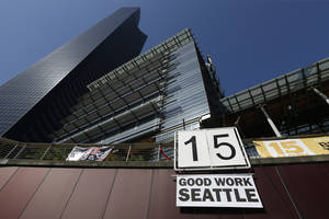 """Photo - A sign that reads """"15 Good Work Seattle"""" is displayed below Seattle City Hall, right, and the Columbia Center building, left, Monday, June 2, 2014, after the Seattle City Council passed a $15 minimum wage measure. (AP Photo/Ted S. Warren)"""