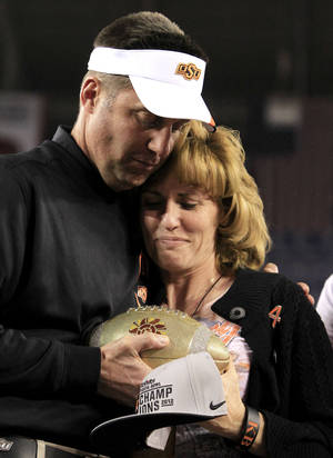 Photo - Oklahoma State head coach Mike Gundy, left, hugs Shelley Budke, wife of former Oklahoma State women's basketball coach Kurt Budke who died in a plane crash in 2011, as Gundy presents the Fiesta Bowl Championship Trophy to her after the Fiesta Bowl NCAA college football game Monday, Jan. 2, 2012, in Glendale, Ariz.  Oklahoma State defeated Stanford 41-38 in overtime.(AP Photo/Ross D. Franklin) ORG XMIT: PNP152