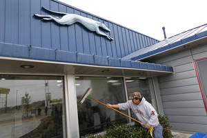 Photo - Jorge Tovar cleans the windows at the new Greyhound bus station at 1948 E Reno. Unlike the Union Bus Station, once controlled by five different bus lines, the new station is controlled by Greyhound, which also coordinates local operations for Jefferson Bus Lines. <strong>Steve Gooch - The Oklahoman</strong>