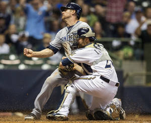 Photo -   San Diego Padres' Chase Headley beats the tag at home from Milwaukee Brewers' Jonathan Lucroy during the seventh inning of a baseball game, Wednesday, Oct. 3, 2012, in Milwaukee. (AP Photo/Tom Lynn)