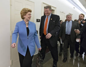 Photo - From left, Senate Agriculture Committee Chair Den. Debbie Stabenow, D-Mich., House Agriculture Committee Chairman Rep. Frank Lucas, R-Okla., and Rep. Collin Peterson, D-Minn., ranking Democrat on the House Agriculture Committee, are intercepted by reporters after negations on the Farm Bill wrapped up on Capitol Hill in Washington, Wednesday, Dec. 4, 2013. There is agreement on many parts of the legislation but significant differences remain over funding for the Supplemental Nutrition Assistance Program, more commonly known as food stamps.  (AP Photo/J. Scott Applewhite)