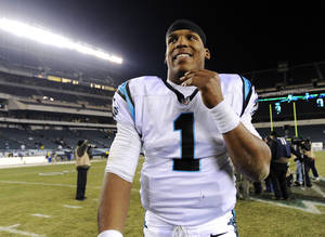 Photo -   Carolina Panthers quarterback Cam Newton smiles as he walks off the field after an NFL football game against the Philadelphia Eagles, Monday, Nov. 26, 2012, in Philadelphia. Carolina won 30-22. (AP Photo/Michael Perez)