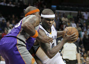 Photo - Memphis Grizzlies' Zach Randolph, right, drives against Phoenix Suns' Jermaine O'Neal during the second half of an NBA basketball game in Memphis, Tenn., Tuesday, Dec. 4, 2012. Randolph scored 38 points in the Grizzlies 108-98 overtime victory. (AP Photo/Danny Johnston)