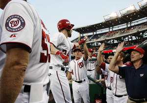 Photo -   Washington Nationals' Bryce Harper, center, celebrates his two-run home run with teammates during the first inning of a baseball game against the St. Louis Cardinals, Thursday, Aug. 30, 2012, in Washington. (AP Photo/Alex Brandon)