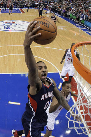 Photo - Atlanta Hawks' Jeff Teague, left, goes up for a shot against Philadelphia 76ers' Evan Turner in the first half of an NBA basketball game, Friday, Dec. 21, 2012, in Philadelphia. (AP Photo/Matt Slocum)