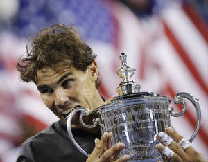 Photo - Rafael Nadal, of Spain, bites the trophy while posing for photos after defeating Novak Djokovic, of Serbia, during the men's singles final of the 2013 U.S. Open tennis tournament, Monday, Sept. 9, 2013, in New York. (AP Photo/David Goldman)