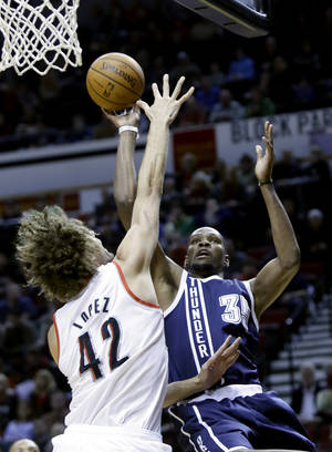 Photo - Oklahoma City Thunder forward Kevin Durant, right, shoots over Portland Trail Blazers center Robin Lopez during the first half of an NBA basketball game in Portland, Ore., Tuesday, Feb. 11, 2014. (AP Photo/Don Ryan)