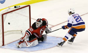 Photo - New York Islanders left wing Matt Moulson (26) scores on New Jersey Devils goalie Martin Brodeur (30) during the shootout in an NHL hockey game Friday, Oct. 4, 2013, in Newark, N.J. The Islanders won 4-3 (AP Photo/Julio Cortez)