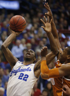 Photo - Kansas guard Andrew Wiggins (22) shoots while covered by Texas forward Jonathan Holmes, right, during the first half of an NCAA college basketball game in Lawrence, Kan., Saturday, Feb. 22, 2014. (AP Photo/Orlin Wagner)