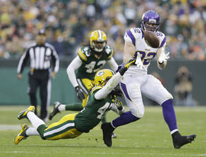 Photo - Minnesota Vikings tight end Kyle Rudolph (82) catches a pass with Green Bay Packers free safety Morgan Burnett (42) defending during the second half of an NFL football game Sunday, Dec. 2, 2012, in Green Bay, Wis. The Packers won 23-14. (AP Photo/Morry Gash)