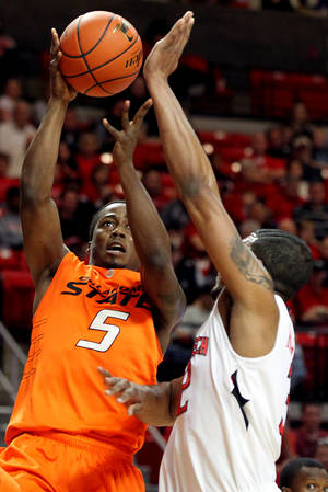 Photo - Oklahoma State's Reger Dowell (5) shoots over Texas Tech's Mike Singletary during their NCAA college basketball game at United Spirit Arena in Lubbock, Texas, Saturday, Jan. 29, 2011. (AP Photo/Lubbock Avalanche-Journal, Miranda Grubbs)