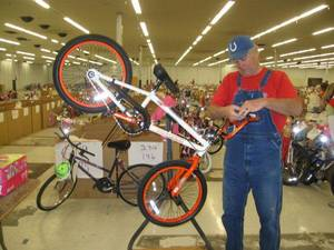 photo - Volunteer Dannie Lamb tightens the handle bars of a donated bike. PHOTO BY PAULA BURKES, THE OKLAHOMAN
