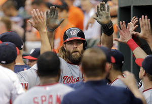 Photo - Washington Nationals' Jayson Werth high-fives teammates in the dugout after scoring on a single by Adam LaRoche in the first inning of an interleague baseball game against the Baltimore Orioles, Wednesday, July 9, 2014, in Baltimore. (AP Photo/Patrick Semansky)