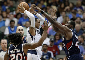 Photo - Dallas Mavericks point guard Monta Ellis, center, attempts to pass the ball under pressure from Atlanta Hawks' Cartier Martin (20), Elton Brand, right, and Pero Antic, rear, of Macedonia, in the first half of an NBA preseason basketball game Wednesday, Oct. 23, 2013, in Dallas. (AP Photo/Tony Gutierrez)